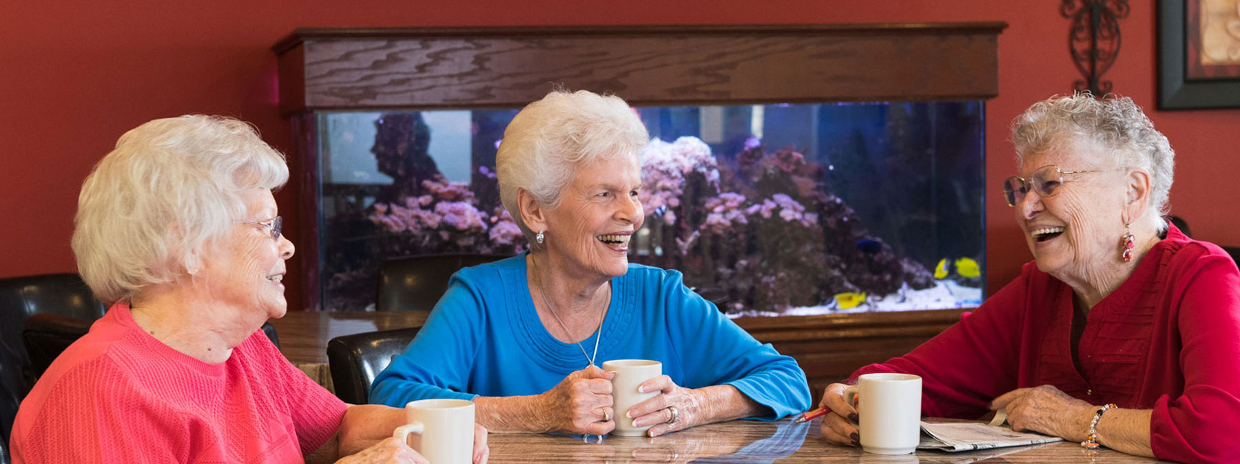 Three women - residents of the Mt. Creek are sitting at a coffee table and having a good time
